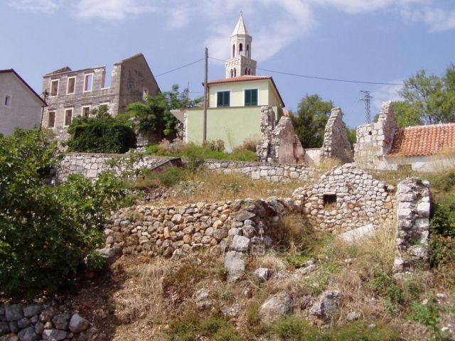 Polorozpadlé domy ve starém městě Podgoře, která se nachází v horách nad novou Podgorou u moře.