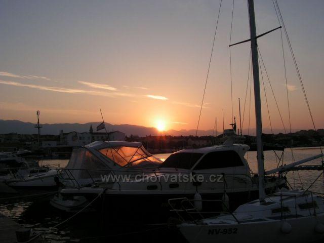 východ slunce nad přístavem v Novalji