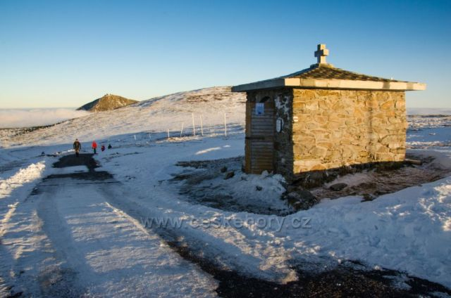 Symbolický památník tragickým obětem hor v bývalé kapličce v Modrém sedle (původně Luční sedlo) ve výšce 1 509 m n. m. mezi Luční a Studniční horou, v pozadí Sněžka (1 602 m n. m.)