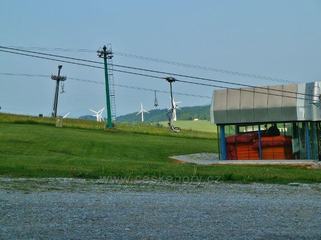 Ramzová - část areálu lanovky na Šerák, v pozadí  vykukují větrné elektrárny v Ostružné