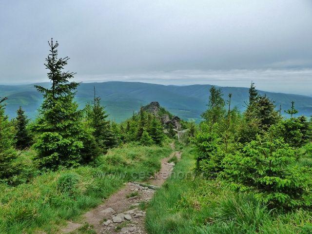 Ramzová - zpětný pohled z turistické stezky na Šerák k Obřím skalám.Na obzoru se rýsují hřebeny Rychlebských hor