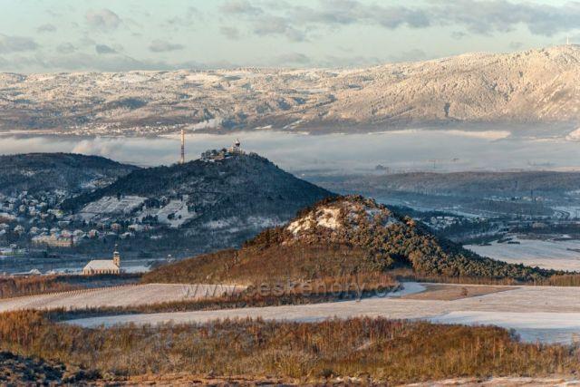 Jedno nádherné mrazivé ráno na vrcholu Zlatníku. V pozadí jsou krásně osvětlené Krušné hory a před nimi mostecký hrad Hněvín.