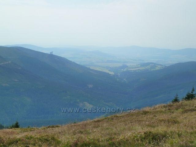 Králický Sněžník - pohled z vrcholu hory k Dolní Moravě.Vlevo je vyčnívá Stezka v oblacích