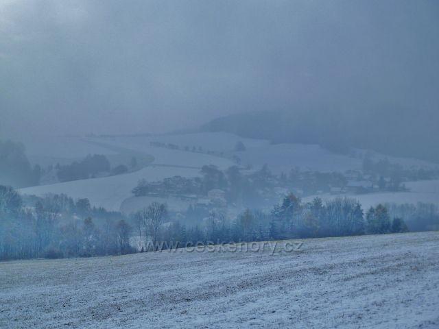Záchlumí - zimní pohled na zamlženou obec z úbočí Chlumu