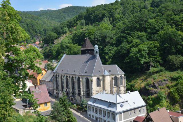 Kostel Nanebevzetí Panny Marie.v pozadí dřevěná zvonice