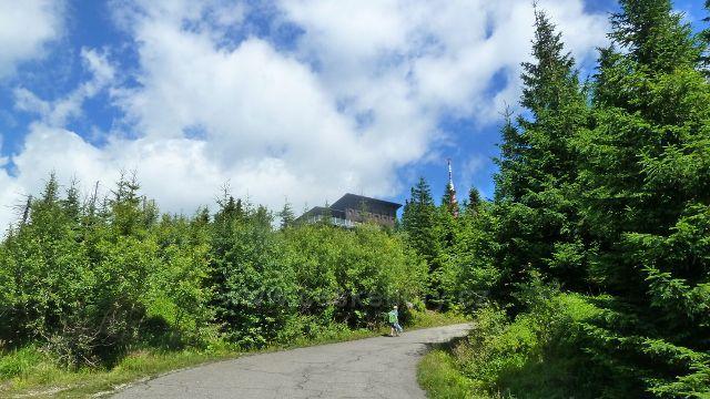 Poslední metry silničky na Lysou horu odkrývají pohled na část nové Bezručovy chaty