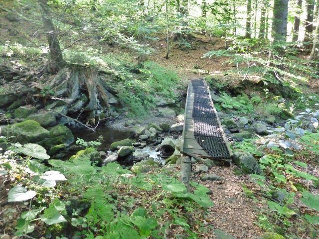 Stezka po mostku přes Suchý potok vede k osadě Muchovice