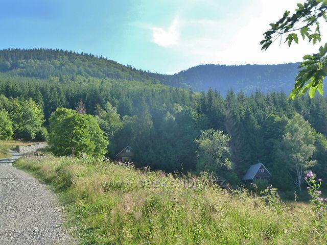 Butořanka - chaty pod trasou NS Lysá hora po červené TZ. Na obzoru vykukuje věž na Lysé hoře.