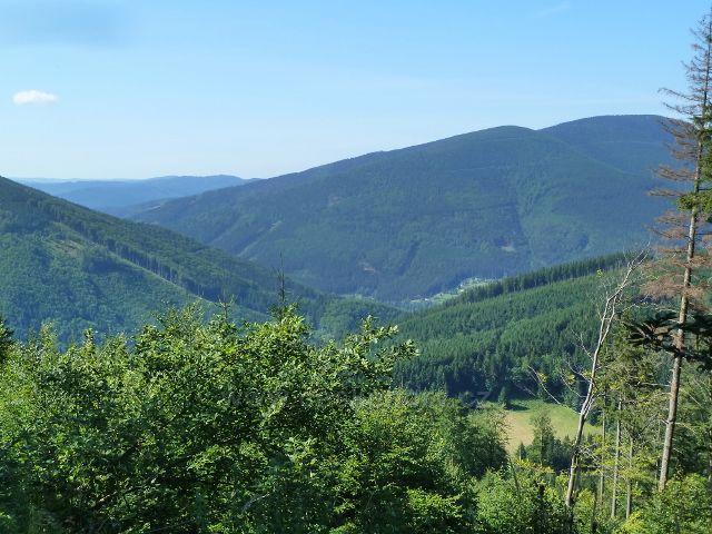 Pohled z cesty po červené TZ z Butořanky na Lukšinec do údolí Mazáku a Ostravice. Vpravo je Malý Smrk a Smrk