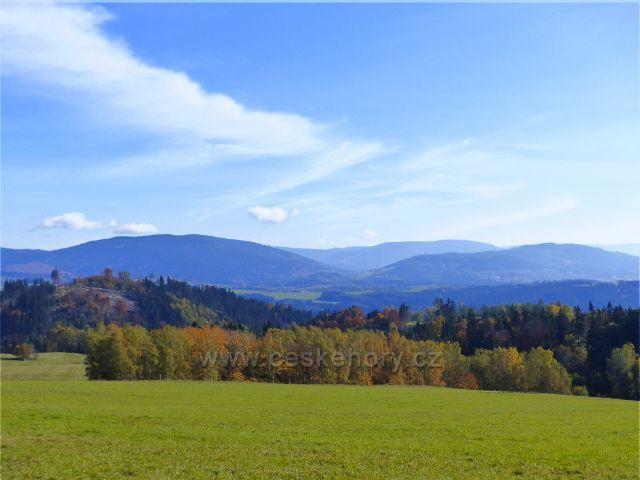 Hynčice pod Sušinou - pohled z cesty okrajem lesa z Chrastic k pásmu Jeseníků a Pradědu, vpředu vystupuje Mlýnský vrch(684 m.n.m.)