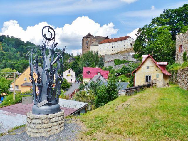 Bečov nad Teplou - pohled z Bečovských schodů na hrad a podhradí. V popředí jeden z výtvorů Kovářského symposia