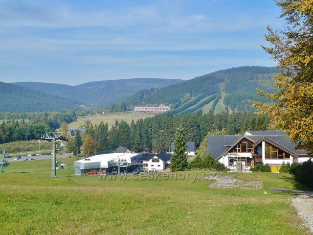 Dolní stanice lanovky z Ramzové na Čerňavu. Na protilehlé straně jsou vrcholky pásma Rychlebských hor