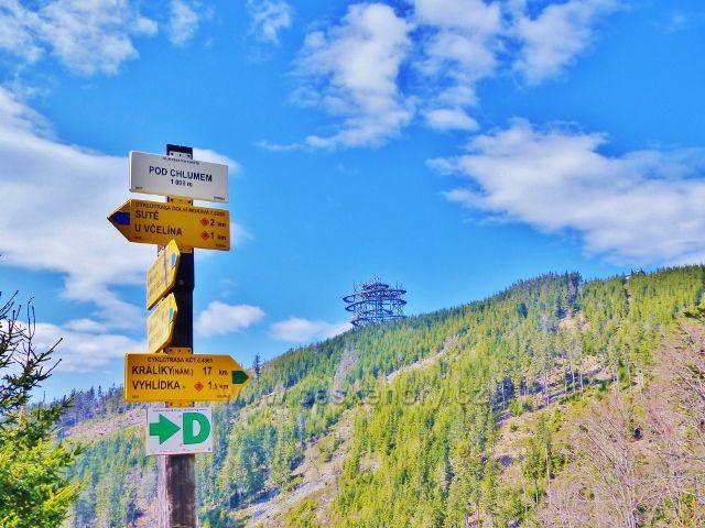 "Turistický rozcestník ""Pod Chlumem 1000 m.n.m"", v pozadí Stezka v oblacích"