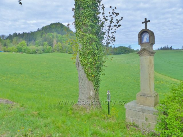 Pomník u silnice do Písečné. V pozadí vidíme hradní vrch Žampach