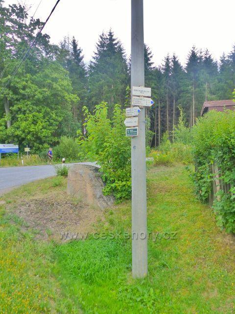 """Turistický rozcestník """"Královec(žst.odb.) 528 m.n.m."""" stojí na křižovatce u silničky do Královického lomu"""