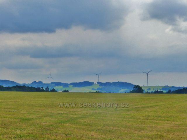 Pohled ze silničky do Královického lomu na větrné elektrárny pod Jánským vrchem nad Zlatou Olešnicí. Vlevo stojí nejvyšší, 125 m vysoká a je zároveň nejvyšší stavbou svého druhu v ČR.Byla vztyčena v roce 2018 a průměr jejího rotoru činí 110 metrů.