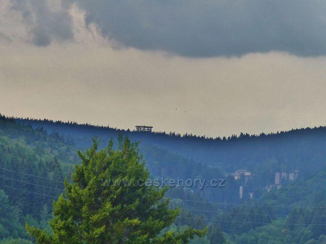 Svoboda nad Úpou - pohled z ulice Sluneční stráň na Stezku v korunách stromů. Pod rozhlednou jsou Jánské lázně.
