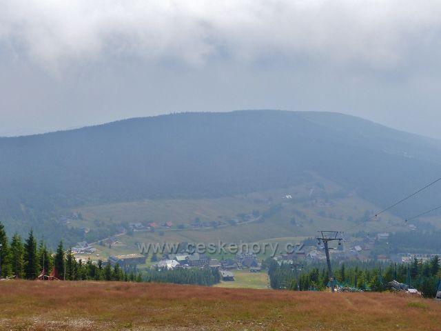 Pohled z vrcholu sjezdovky skiareálu Pomezní boudy na Horní Malou Úpu a nad ní se tyčící Pomezní hřeben s vrchem Lysočina (1188 m.n.m.)