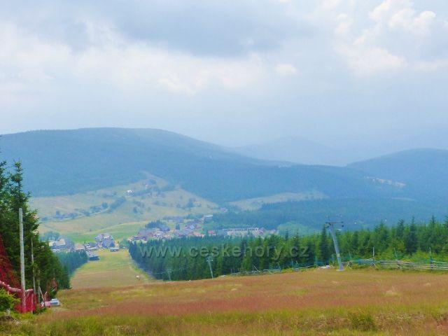 Pohled na sjezdovku skiareálu Pomezní boudy a Horní Malou Úpu.Nad údolím vystupuje Hraniční hřeben