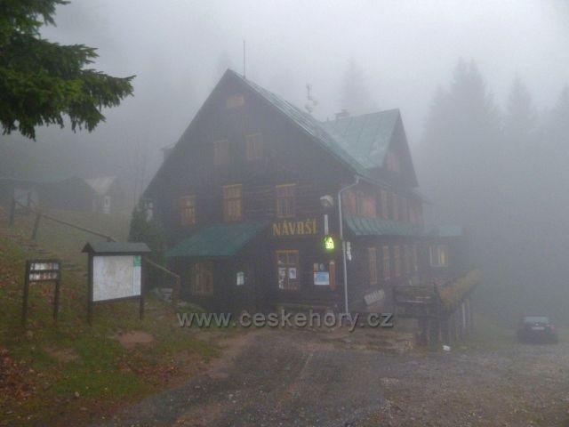 Králický Sněžník - horská chata Návrší nad obcí Stříbrnice v podzimním šeru a obklopena mlhou