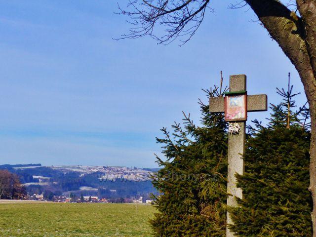 Kamenný kříž u silničky do Bystřece. Na obzoru obec Sobkovice