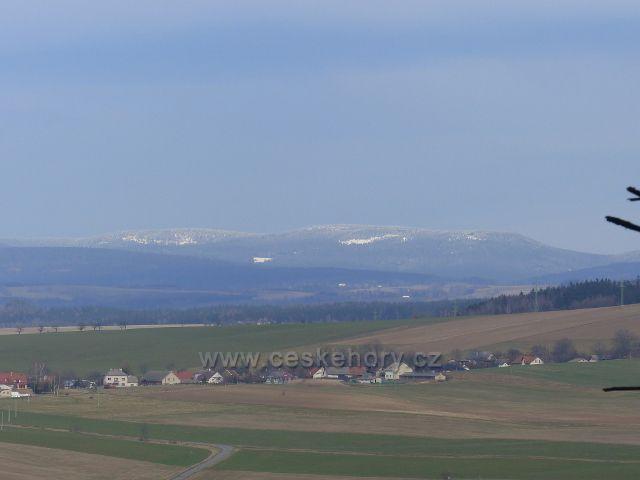 Potštejn - pohled ze silnice od kamenolomu do Potštejna na zasněžený hřeben Orlických hor. V popředí je část obce Merklovice