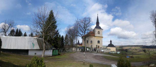 Kolem kostela se rozkládá hřbitov. Vlevo je budova staré školy z konce 17. století.