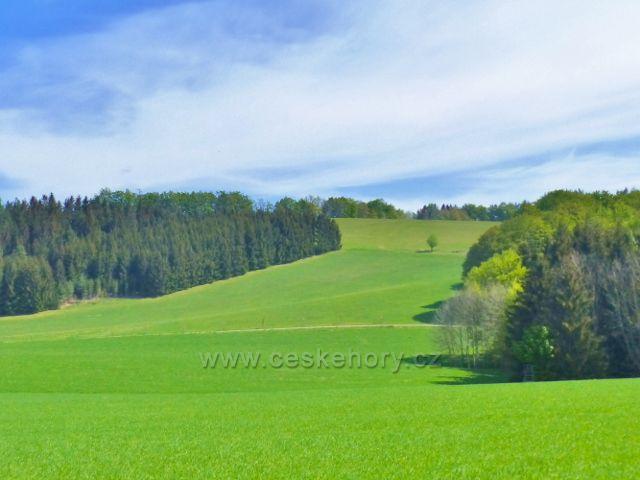 Hejnice - pohled z cesty na Žampach na vrchol protilehlého Kozince (544 m.n.m.) a pod ním jdoucí silničku k Písečné