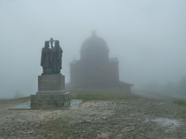 Sousoší sv. Cyrila a Metoděje na vrcholu Radhoště (1129 m.n.m.) před z mlhy vystupující kaplí zasvěcené těmto věrozvěstcům