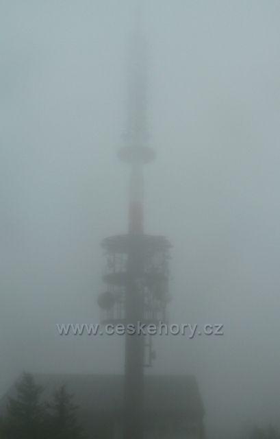Vysoká věž televizního dokrývače Valašské Meziříčí na vrcholu Radhoště nesměle proráží mlhou