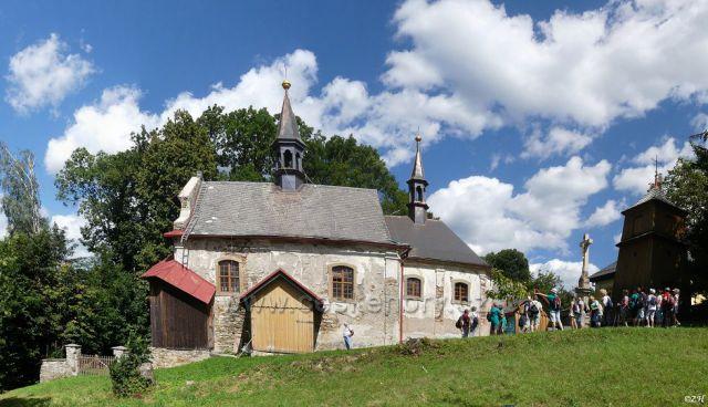 Kostel sv. Jana Nepomuckého s obnoveným křížem a dřevěnou zvonicí