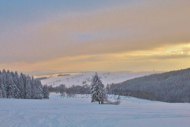 Bartošovice v O.h. podvečerní pohled od turistického přístřešku Vysoký Kořen na zasněžené pastviny Vrchní Orlice.V pozadí je úbočí Polomu