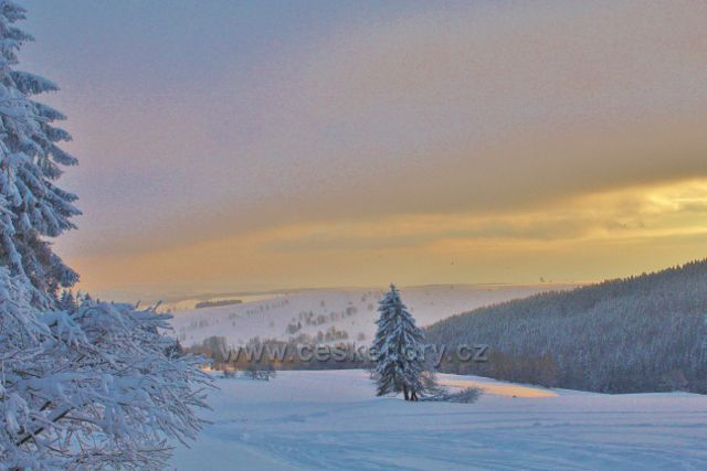 Bartošovice v O.h. -podvečerní pohled z výhledového místa na Vysokém Kořenu na hřeben Polomu. Vpředu jsou pastviny nad Vrchní Orlicí
