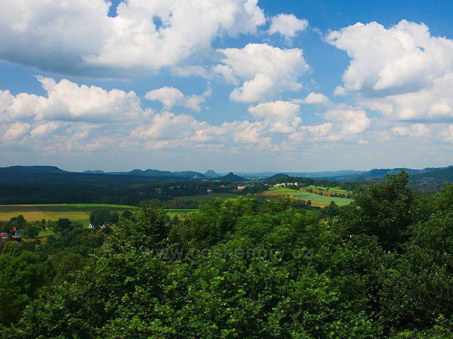 Výhled z rozhledny Růženka na Pastevním vrchu. Uprostřed obec Janov, za ní výrazné vrcholy Zirkelstein a Lilienstein.