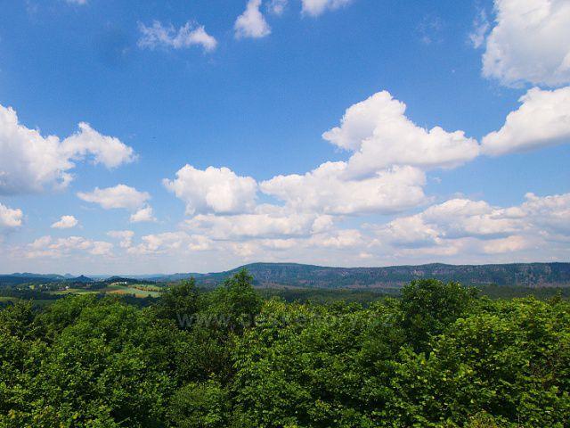 Výhled z rozhledny Růženka na Pastevním vrchu. U levé strany na obzoru výrazné vrcholy Zirkelstein a Lilienstein, od středu doprava Stříbrné stěny a okolí Pravčické brány.