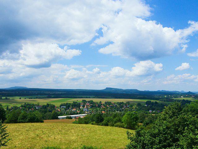 Výhled z rozhledny Růženka na Pastevním vrchu. U levé strany na obzoru Děčínský Sněžník, vravo od středu Velký a Malý Zschirnstein, u levého okraje výrazné vrcholy  Lilienstein a Zirkelstein.